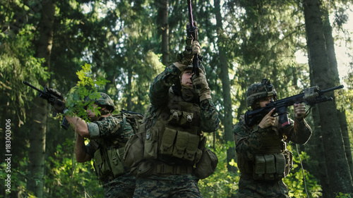 Three Fully Equipped Soldiers Wearing Camouflage Uniform