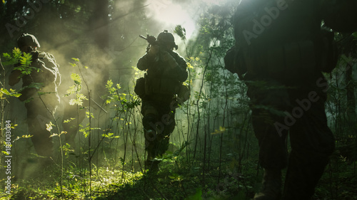Fotomural  Fully Equipped Soldiers Wearing Camouflage Uniform Attacking Enemy, Rifles Ready to Shoot