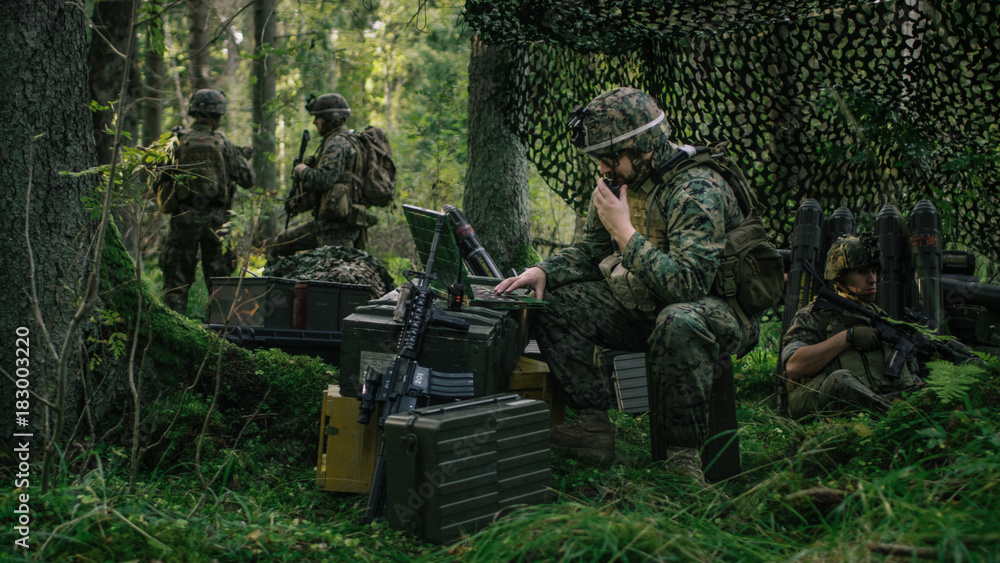 Fototapeta Military Staging Area, Chief Engineer Uses Radio and Army Grade Laptop. Forest Operation/ Mission in Progress.