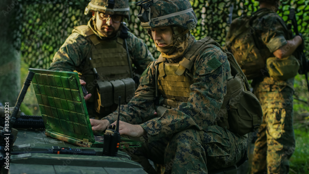 Fototapeta Military Staging Base, Officer Gives Orders to Chief Engineer, They Use Radio and Army Grade Laptop. They're in Camouflaged Tent in a Forest. They're on Reconnaissance Operation/ Mission.