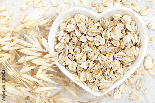 Oat groat in heart shaped bowl, oatmeal grain for healthy