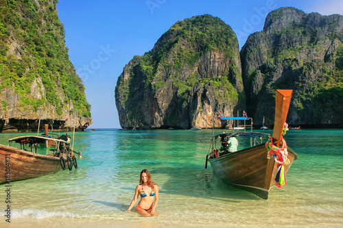 Foto op Canvas Eiland Young woman sitting on the beach at Maya Bay on Phi Phi Leh Island, Krabi Province, Thailand