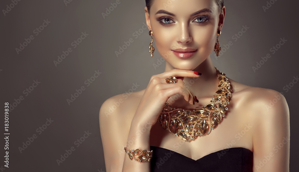 Fototapeta Beautiful girl with set jewelry .   Woman in a necklace with a ring, earrings and a bracelet. Beauty and accessories.