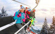 canvas print picture - cheerful friends are lifting on ski-lift for skiing in the mountains