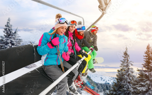 plakat cheerful friends are lifting on ski-lift for skiing in the mountains