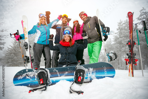 friends skiers and snowboarders having fun on snowbound winter forest