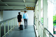 Young business leader concept. Young business man and woman walking down the street in urban city with woman holding a roller bag.
