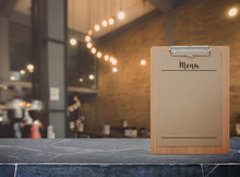 Blank Menu Paper Notepad On Stone Table Top At Coffee Shop Interior Background,Template Mock Up For Adding Your Design.