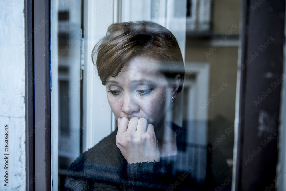 Fototapeta dramatic close up portrait of young beautiful woman thinking and  feeling sad suffering depression at home window looking depressed