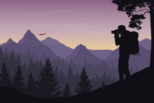 A Tourist Photographing A Flying Bird In A Mountain Landscape With Forest Under A Morning Sky With Dawn And Clouds