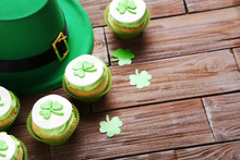 Delicious Cupcakes With Hat On Brown Wooden Table. St. Patricks Day