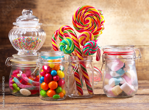 Colorful candies, lollipops and marshmallows in a glass jars