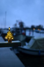 A Little Christmas Tree In A Port With Ships And Boats