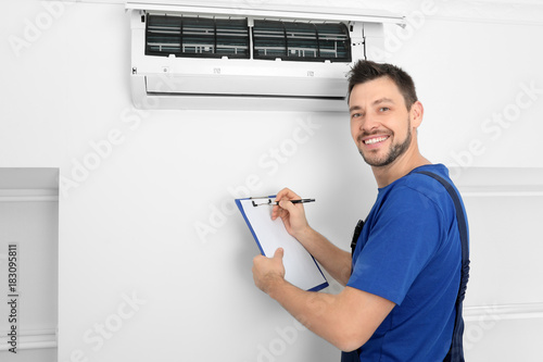 Fotomural Male technician checking air conditioner indoors