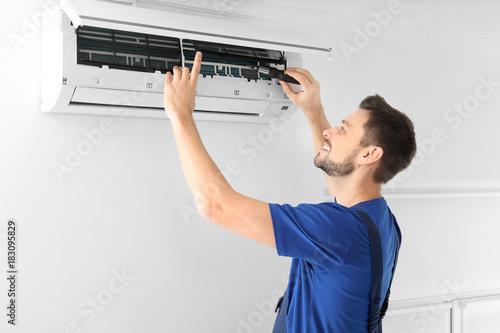 Fotografía  Male technician repairing air conditioner indoors