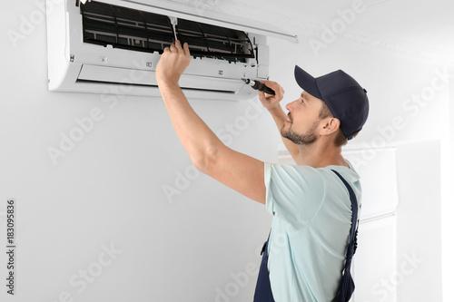 Cuadros en Lienzo  Male technician repairing air conditioner indoors