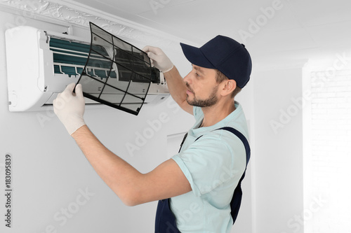 Fotomural Male technician cleaning air conditioner indoors