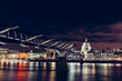 Long exposure of Millennium Bridge and London city skyline on River Thames at night