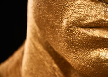 Man In Gold Paint. Detail Of A Man's Face Courageous Lips, Neck And Chin.