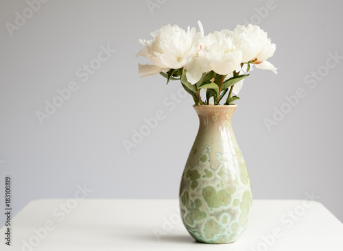 Closeup Of White Peonies In Green Vase On Table Against Grey