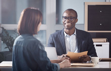 Glad To Hear It. Portrait Of Optimistic Young Qualified African Manager Is Looking At His Colleague Female With Smile While Sitting At Table And Having Pleasant Communication. Back View Of Woman