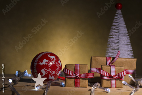 christmas gifts and ornaments on table golden background