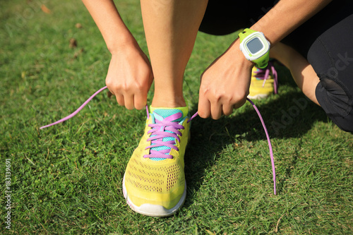 Young fitness woman tying shoelace at on meadow Tableau sur Toile