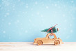 Wooden toy car with Christmas tree on the roof on a blue background with a snowfall. Copy space.