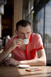 Man drinking coffee sitting at table by the window