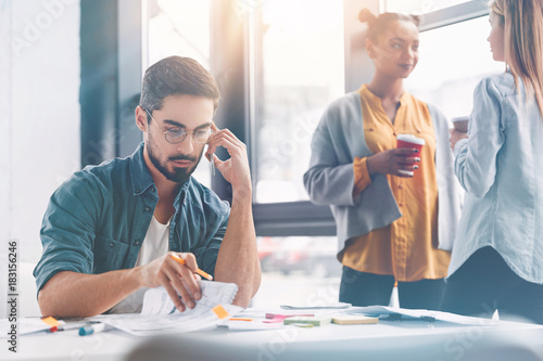Professional coworkers meet together to discuss future plans, brainstrom and check accountings. Bearded handsome man analyzes information with partner on smart phone, women have talk in background
