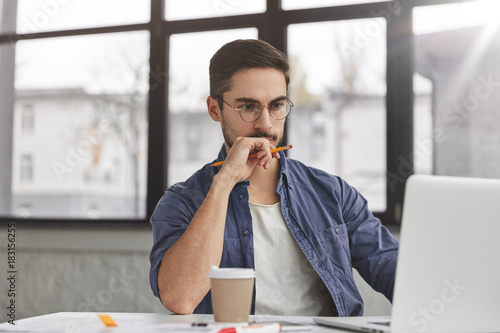 View of concentrated talented skilled male focused on screen of laptop computer, reads necessary information for creating budget report, drinks hot beverage. Attractive male freelancer keyboards text