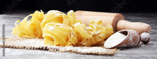 Making homemade pasta linguine on rustic kitchen table with flour, rolling pin and pasta.