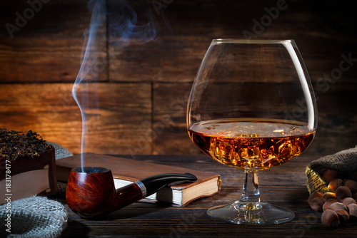 Photo Glass of whiskey with ice, notebook and smoking pipe on a old wooden table