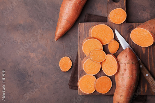 Raw sweet potatoes on wooden kitchen board top view. Organic food.