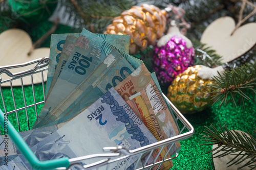 Christmas expenses / concept / Brazilian money, reais in the shopping cart and holiday decorations