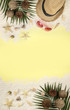 Summer concept and accessories(shells, starfish, coconut leaf)with sandy beach on yellow background.