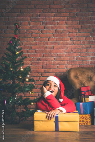 Little smiling Indian girl with christmas gifts while wearing santa