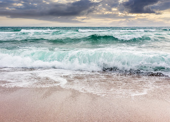 Fototapetaseascape in stormy weather at cloudy sunrise. green waves crashing on golden sand of the beach