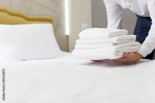 hotel staff setting up pillow on bed Wallpaper Mural