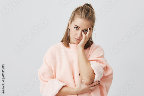 Photo Bored European girl student wearing stylish pink sweatshirt touching face with hand, looking annoyed, tired of listening uninteresting stories