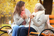 canvas print picture - Senior woman with cane and young caregiver sitting on bench in park