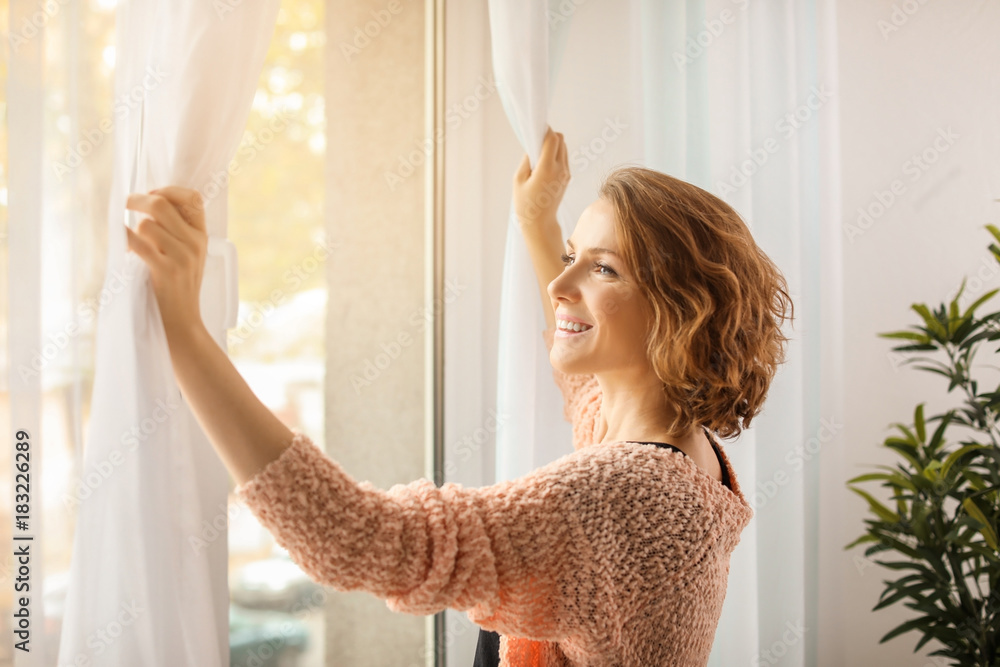 Fototapety, obrazy: Beautiful woman opening curtains at home
