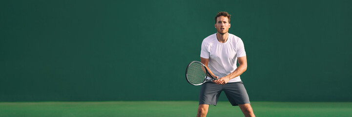 Fototapeta Tennis player man focused in ready position. A male athlete waiting for serve on panoramic green background banner. Challenge and concentration in competition.