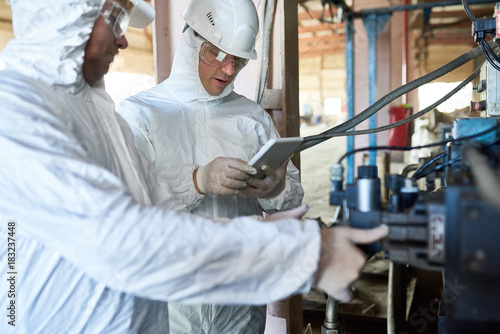 Fotografie, Obraz  Portrait of two factory workers wearing biohazard suits operating machine via di