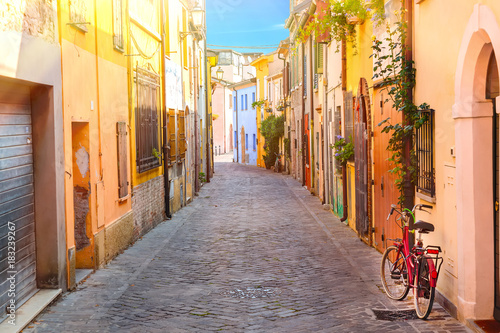 Canvas Prints Narrow alley Narrow street of the village of fishermen San Guiliano with colorful houses and a bicycle in early morning in Rimini, Italy