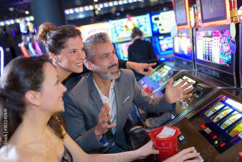 Fotografie, Tablou friends in casino on a slot machine