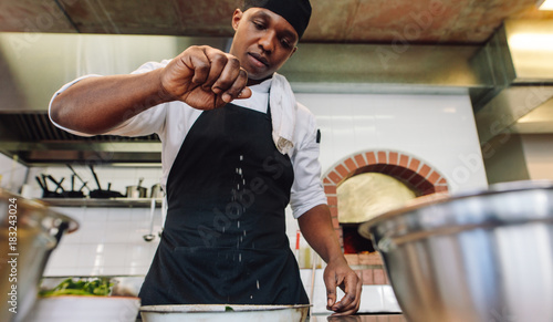 Fotografía  Chef sprinkling spices on dish in commercial kitchen