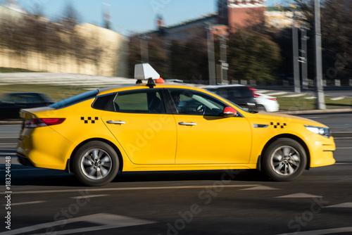 Żółty samochód taxi w ruchu na ulicy miasta