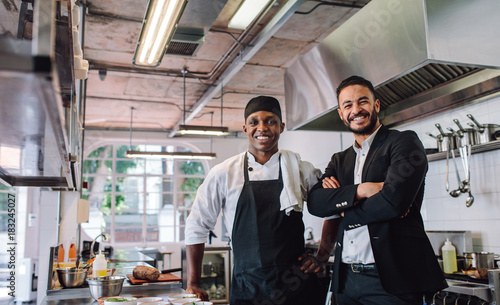 Spoed Foto op Canvas Restaurant Restaurant owner with chef in kitchen