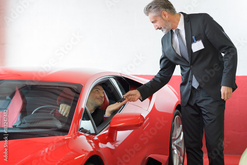 Photo  client and seller talking about lamborghini at luxury car dealer